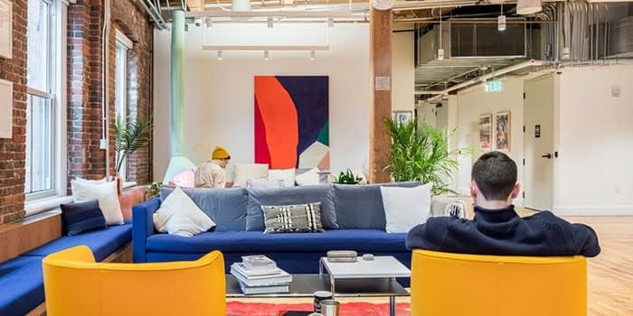 WeWork Boston office with a blue sofa, yellow chairs, plants and a big colorful painting