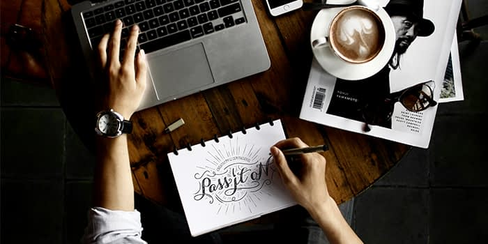 Person doodling a logo in notebook