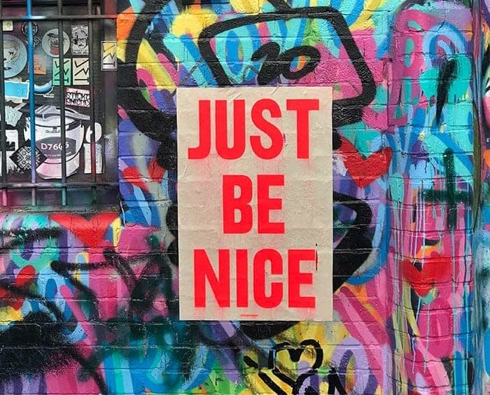 Just be nice poster on a wall covered in graffiti in London