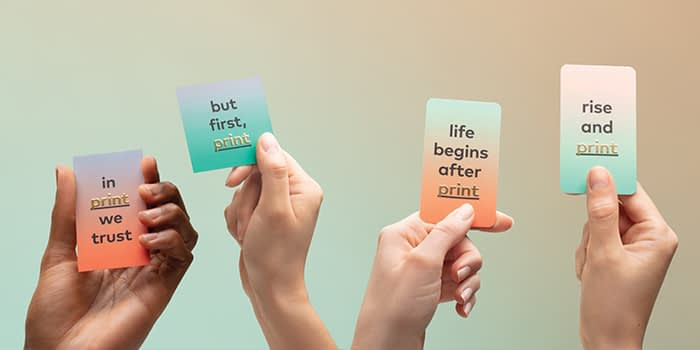 Hands holding gradient business cards with a foil message