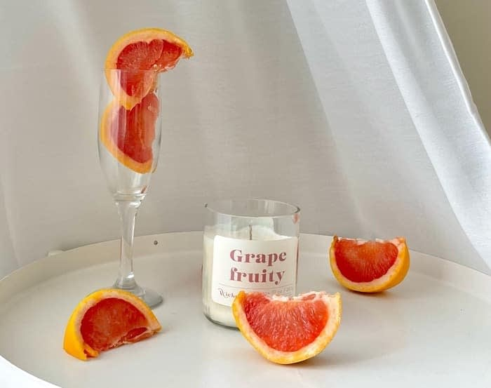 Grapefruit candle by Wickend surrounded by grapefruit slices