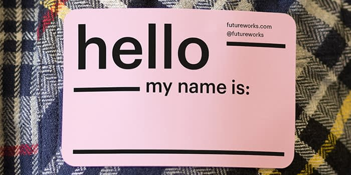 moo brand stickers being used as an icebreaker for trade shows and events. the name tag sticker reads hello my name is, with a space for a fact. the name tag sticker is printed on a business sticker in pink