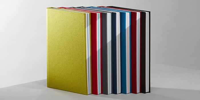 7 hardback notebooks with colorful cloth covers and colored central pages