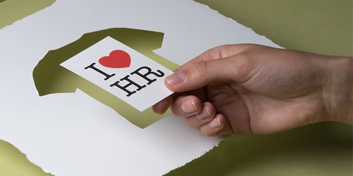 Hand taking a recycled business cards saying I love HR from a sheet of recycled cotton paperwith a t-shirt shaped cutout