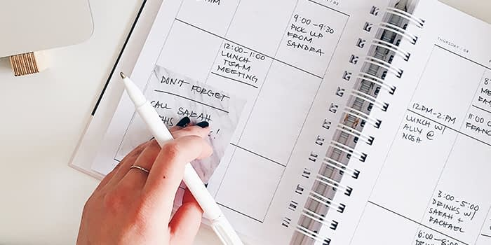 Writing with a pen in a busy daily planner