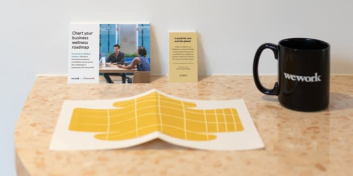 Yellow paper face mask on a desk with a postcard and a business card by MOO