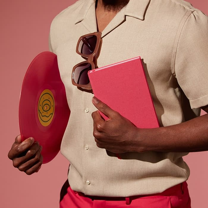 Person holding a pink notebook and a frisbee