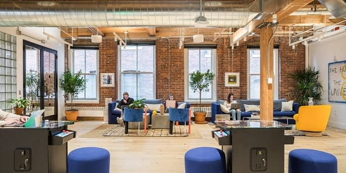 Boston WeWork office with brick walls and people working from blue couches and chairs