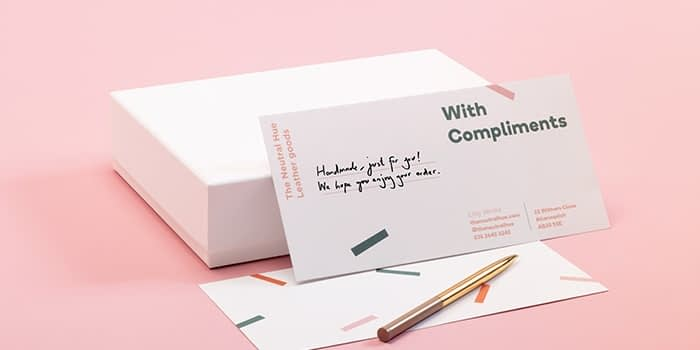 Pen and note card with handwritten message standing on a white box. The card says with compliments and makes use of white space with a minimalist design.