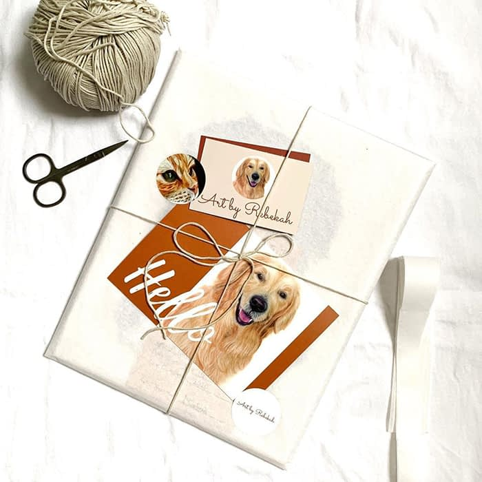 Ball of wool, scissors and packaging with a Hello dog postcard, a dog business card and a cat round sticker by pet portrait artist Rebekah Mushinski