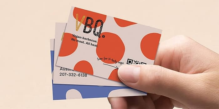 Hand holding 3 QR code business cards
