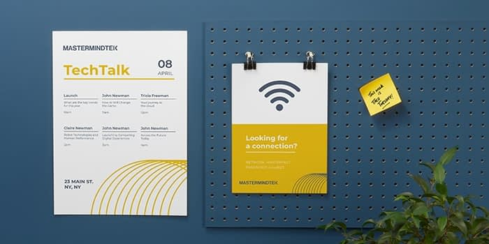 Poster for a talk on the wall and WiFi flyer on a notice board in a tech company office. The prints are mustard and white and make use of negative space to make titles and icon stand out. There is a post-it on the notice board and a house plant in the corner.