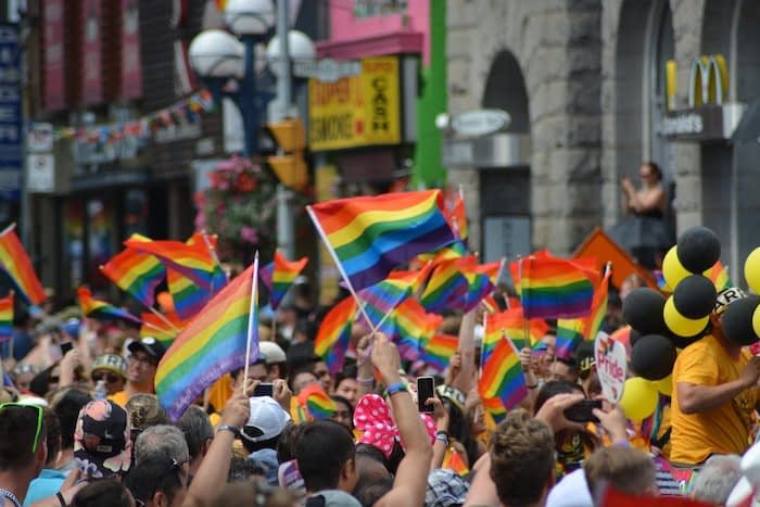 Crowd of people celebrating Pride on the street with raimbow flags designed by Gilbert Baker