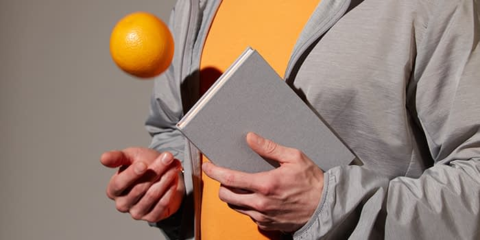 Person juggling with an orange and holding a light grey notebook