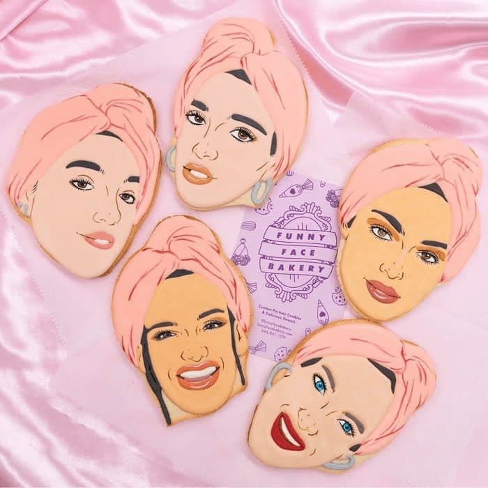 5 decorated cookies with the faces of women with a pink turban and purple Funny Face Bakery business card on a pink satin background