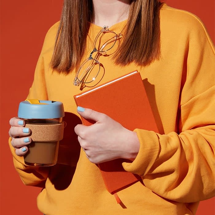 Woman dressed in orange carrying an orange hard cover notebook