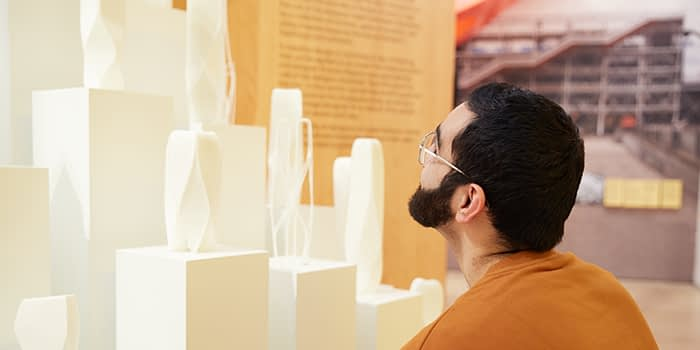 MOO employee looking at sculptures in the London design museum