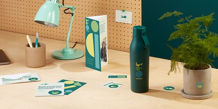 Custom green water bottle, print materials with green branding and green lamp on a desk