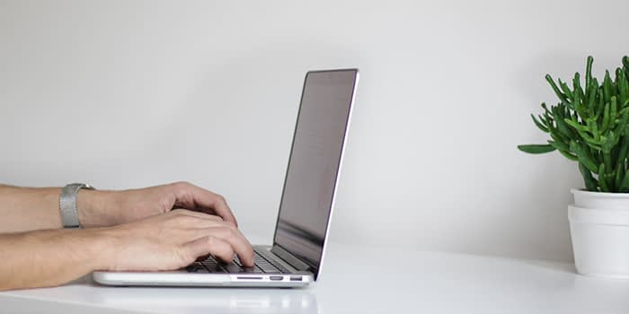 man typing on his laptop with neutral background for video call