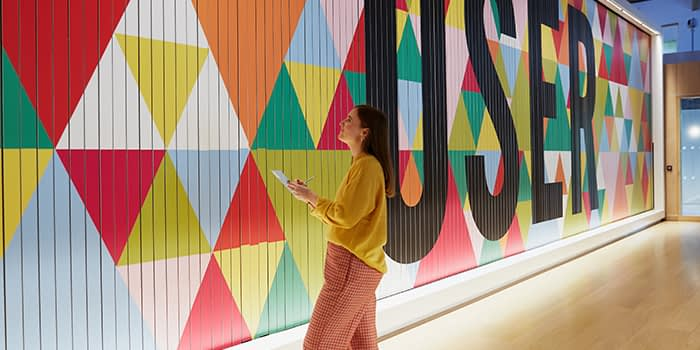 Em taking notes in front of a colorful mural with the word user