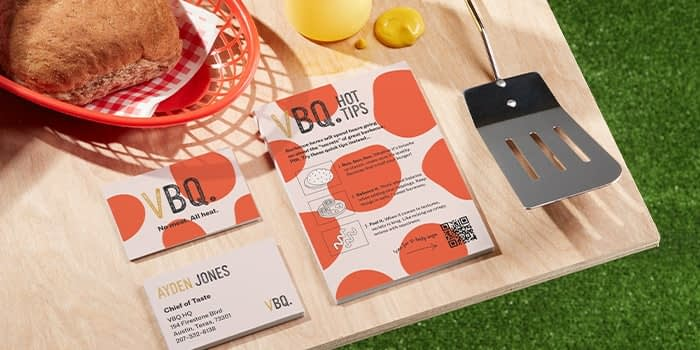 Flyer with cooking instructions and QR code business cards with a fun red dots design on a barbecue table by fake vegan brand VBQ