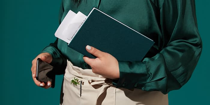 Person carrying a green hardbound notebook and a phone